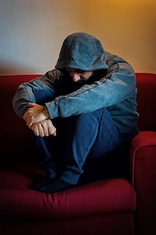 Przygnębiony mężczyzna z kapturem na głowie, siedzący samotnie na kanapie.
