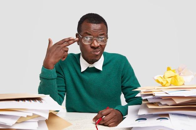 Przygnębiony młody afroamerykanin wykonuje gest samobójczy w skroni, zaciska usta z niezadowoleniem, trzyma czerwony długopis, nosi elegancki strój