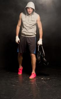 Przygnębiony młody bokser wychodzący po klęsce w bluzie z kapturem i trzymający w zabandażowanych rękach rękawiczki