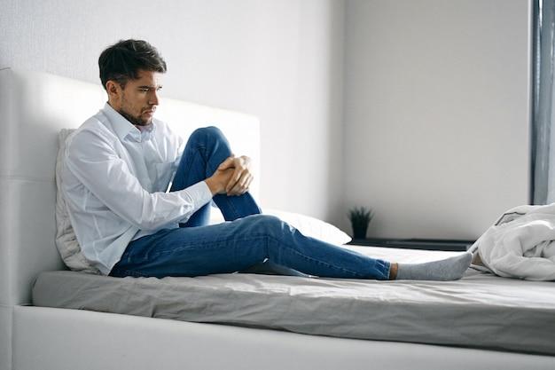 Przygnębiony młody człowiek siedzi na łóżku