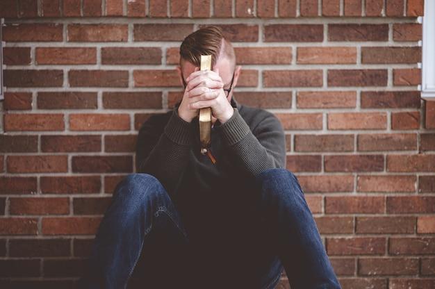 Przygnębiony młody mężczyzna siedzi na ziemi na ścianie, trzymając pismo święte