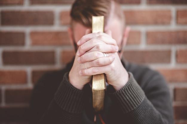 Przygnębiony młody mężczyzna siedzi na ziemi pod ścianą, trzymając pismo święte