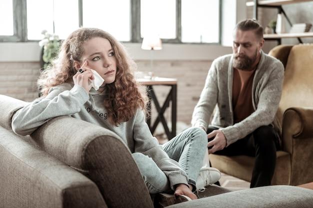 Przygnębiony nastolatek. ciemnowłosa piękna nastolatka czuje się przygnębiona rozmawiając z prywatnym terapeutą
