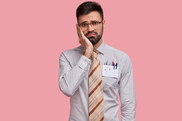 Przygnębiony, nieogolony mężczyzna trzyma rękę na policzku, nosi formalne ubranie, ma długopisy w kieszeni, patrzy z żałosnym wyrazem twarzy