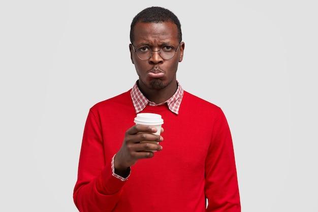 Przygnębiony niezadowolony facet ma ciemną skórę, żałosny wyraz twarzy, zaciska usta z niezadowoleniem, pije i wyjmuje kawę