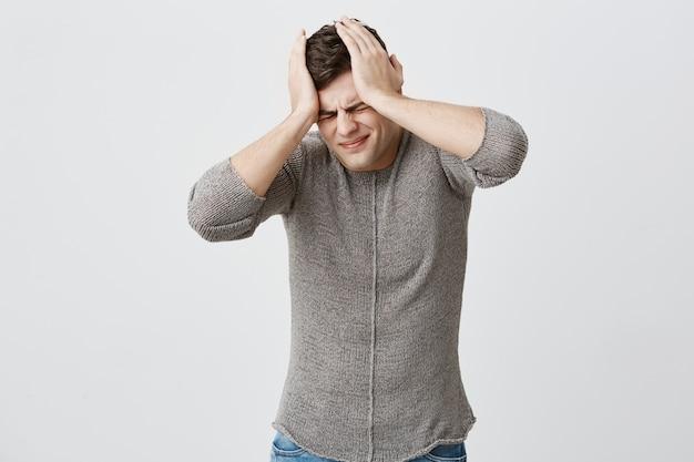 Przygnębiony, pełen niedowierzania, muskularny mężczyzna o ciemnych włosach w swetrze, trzymający się za ręce na głowie, mający beznadziejną sytuację życiową i trudny wybór. przerażony przygnębiony młody człowiek