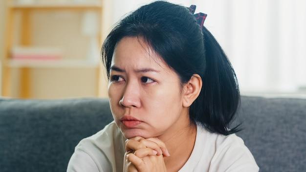 Przygnębiony płacz azjatycka kobieta stresująca się z bólem głowy siedzi na kanapie w salonie w domu