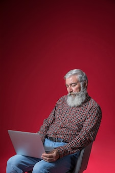 Przygnębiony starszy mężczyzna za pomocą laptopa na czerwonym tle