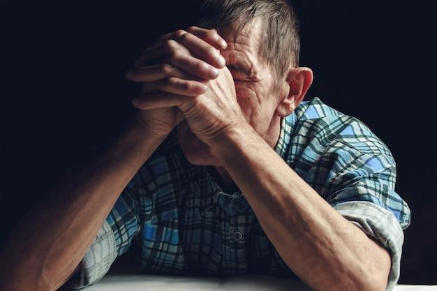 Przygnębiony starszy mężczyzna zakrywa twarz rękami.