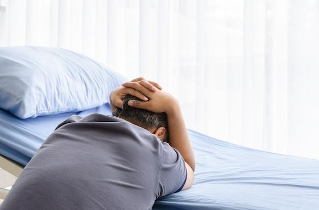 Przygnębiony starszy współmałżonek żałobny na łóżku pacjenta po zmarłej żonie w szpitalnej sali