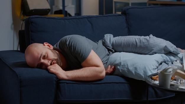 Przygnębiony zawiedziony mężczyzna ze złamanym sercem z powodu rozstania, płacz obficie leżący na kanapie ha...