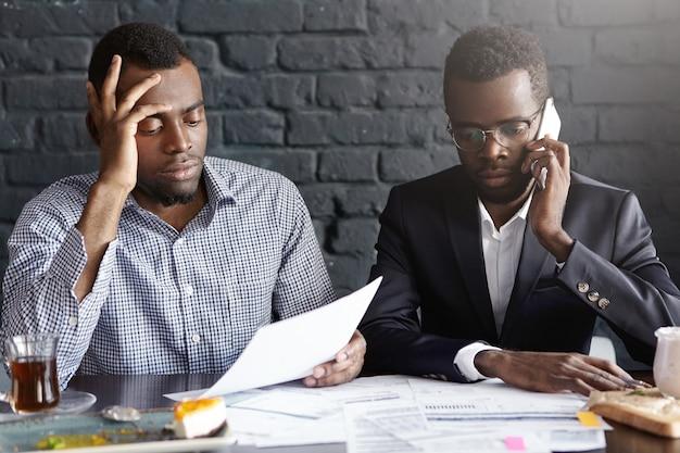 Przygnębiony zdenerwowany african-american biznesmen rozmawia przez telefon komórkowy