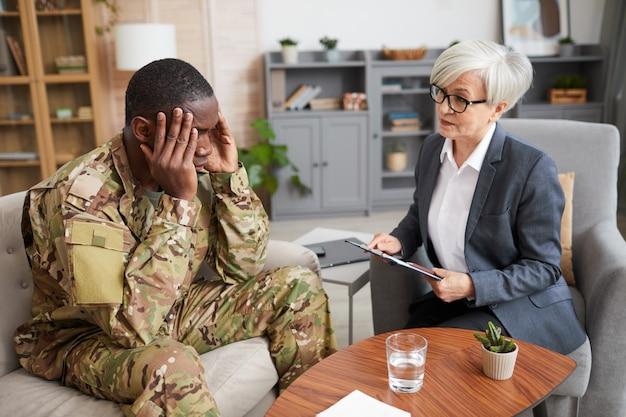 Przygnębiony żołnierz siedzący na kanapie, trzymając głowę rękami i rozmawiając z psychologiem podczas spotkania