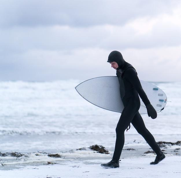 Przygoda surfer na plaży zima śnieg