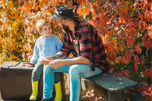 Przygoda z synem. opowiadanie historii o minionych czasach. ojciec z walizką i jego syn.