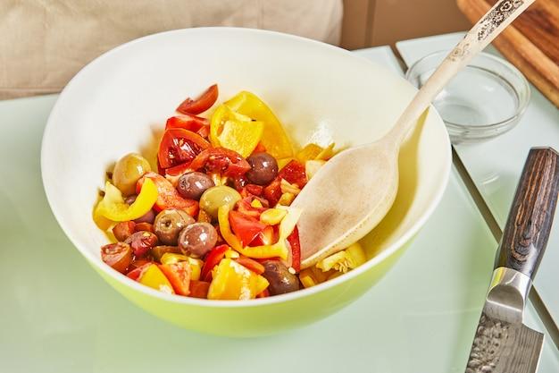 Przygotowana sałatka z oliwek z nauki online, z cyfrowym przepisem na tablet dotykowy podczas przygotowywania zdrowych posiłków w domowej kuchni