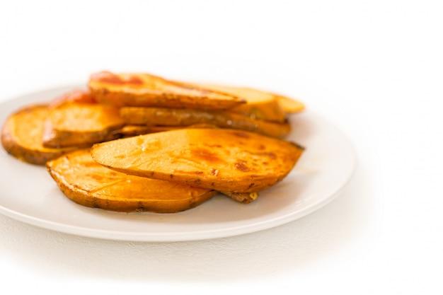Przygotowane smażone plastry słodkich ziemniaków leżą w środku stołu. pieczony korzeń. kuchnia. szef kuchni. gotowanie dla wegan. smaczne danie. przepis. mniam tosty ze skórką. pomarańczowy