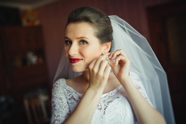 Przygotowania dla nowożeńców do ceremonii ślubnej. narzeczona zakładanie biżuterii