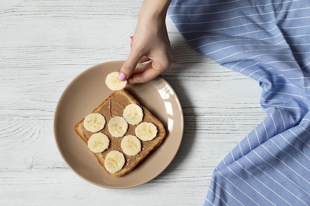 Przygotowanie amerykańskiego śniadania, tosta z białego chleba z masłem orzechowym i plasterkami banana