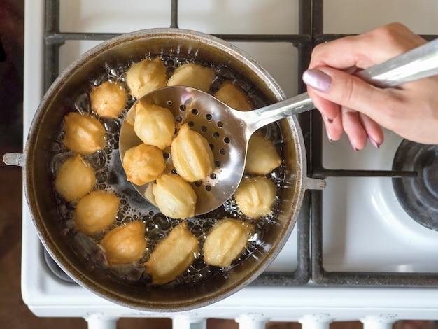 Przygotowanie arabskiego deseru tulumba we wrzącym oleju. tulumba - smażony miód z gąbki w syropie arabskim.