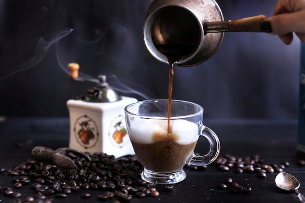 Przygotowanie aromatycznej kawy z pianką i mlekiem. ciemne zdjęcie. turecka kawa. skopiuj spce