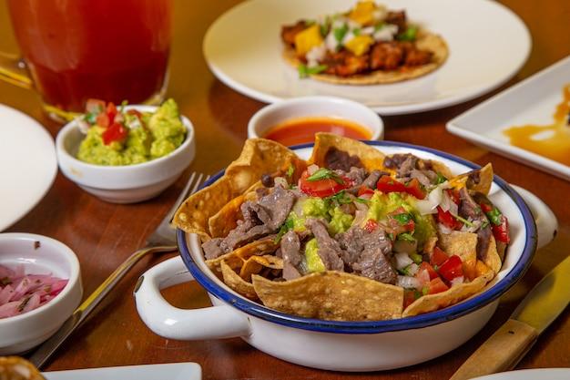 Przygotowanie autentyczne meksykańskie nachos na drewnianym stole.