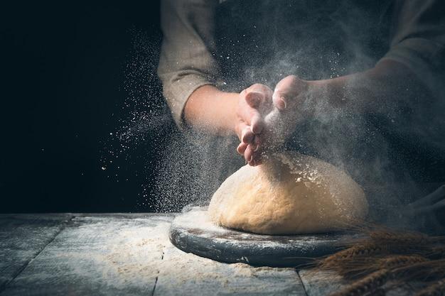 Przygotowanie chleba. zagnieść ciasto w chmurze pyłu z mąki.