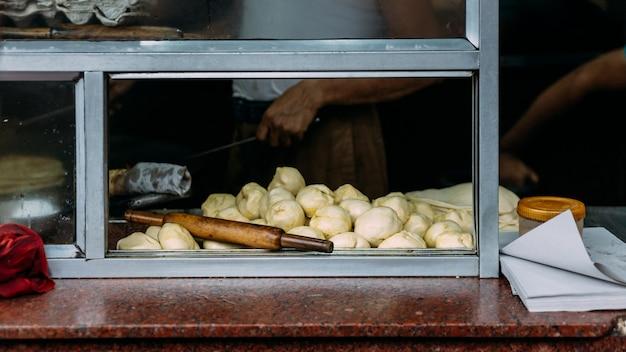 Przygotowanie ciasta na blacie kuchennym do robienia kurczaka kati. uliczne jedzenie w kalkucie w indiach.