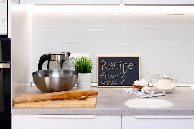 Przygotowanie ciasta na chleb lub domowe wypieki. składniki na stole. tablica z przepisami