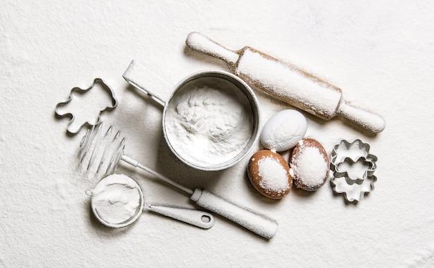 Przygotowanie ciasta. narzędzia do ciasta - wałek do ciasta, trzepaczka, sito, foremki w mące. widok z góry