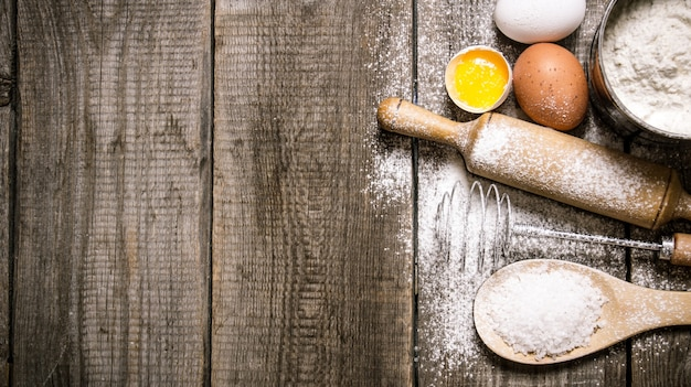Przygotowanie ciasta. składniki na ciasto - jajka i mąka z wałkiem do ciasta. na drewnianym tle. wolne miejsce na tekst. widok z góry
