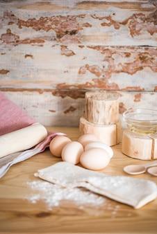 Przygotowanie ciasta. składniki na ciasto - jajka i mąka z wałkiem do ciasta. na drewnianym tle