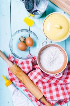 Przygotowanie ciasta. składniki na ciasto - jajka i mąka z wałkiem do ciasta. na drewnianym tle.
