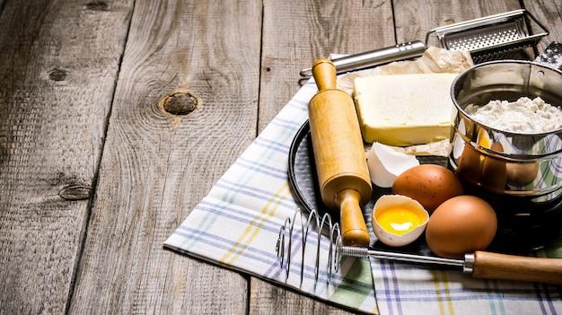 Przygotowanie ciasta. składniki na ciasto - jajka, masło, mąka, sól i narzędzia na tkaninie. na drewnianym tle.