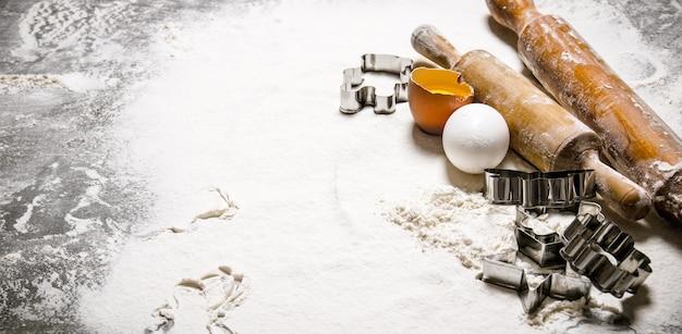 Przygotowanie ciasta. składniki na ciasto - jajka z mąką i wałki do ciasta. na kamiennym stole. wolne miejsce na tekst.