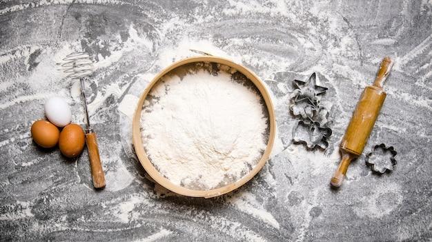 Przygotowanie ciasta. składniki na ciasto - mąka na sicie, jajka i wałek do ciasta z foremkami. na kamiennym stole. widok z góry