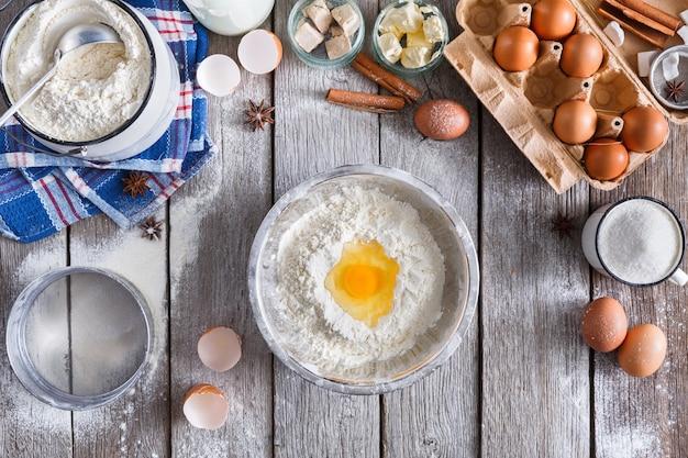 Przygotowanie ciasta widok z góry. napowietrzne żółtko na mące. gotowanie składników do ciasta na rustykalnym drewnie, lekcje kulinarne lub koncepcja przepisu.