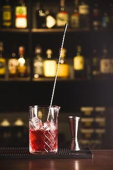 Przygotowanie czerwonego koktajlu na pasku w pięknym szklance.