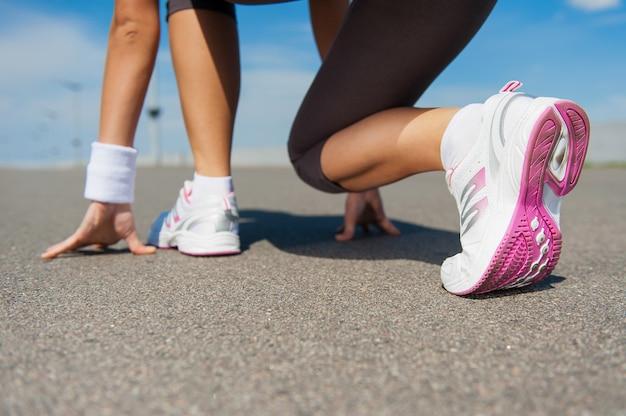 Przygotowanie do biegu. zbliżenie kobiety w butach sportowych stojącej na linii startu