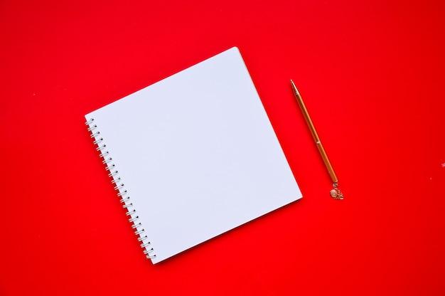 Przygotowanie do bożego narodzenia i nowego roku biały notatnik i złoty długopis są izolowane na czerwono