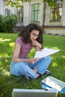 Przygotowanie do egzaminów. śliczna młoda ciemnoskóra dziewczyna przygotowuje się do egzaminów w parku