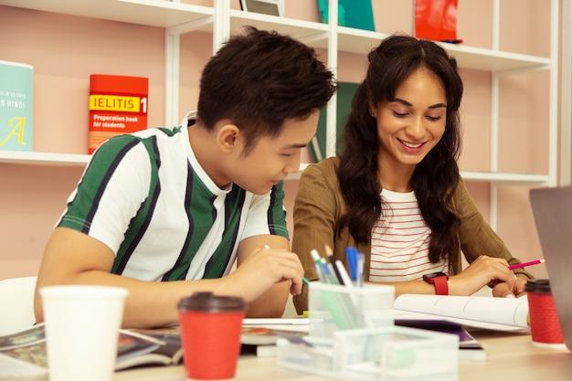 Przygotowanie do egzaminu. dość długowłosa dziewczyna, patrząc na swój zeszyt, uśmiecha się na twarzy