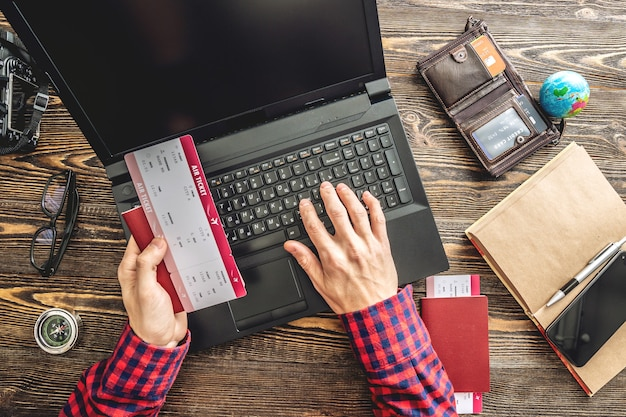 Przygotowanie do ekscytującej podróży. mężczyzna rezerwuje loty, pisząc na laptopie i płacąc kartą kredytową na drewnianym tle