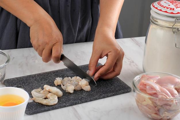 Przygotowanie do gotowania: kobieta szefa kuchni mielone krewetki/krewetki z nożem na czarnej desce do krojenia w kuchni. krok po kroku robienie pierogów/dim sum z kurczakiem i krewetkami