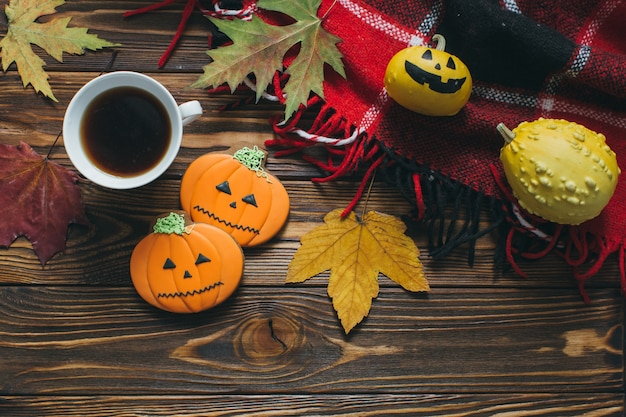 Przygotowanie do halloween: dekoracja jesienna, dynie, kratę, liść, piernik i kawę.
