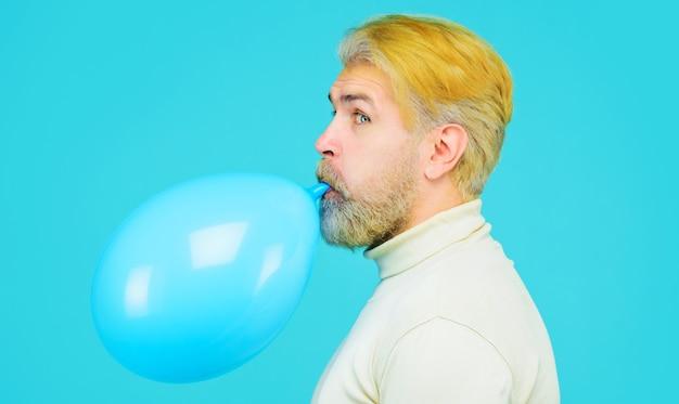Przygotowanie do imprezy. brodaty mężczyzna dmuchanie balonem. wszystkiego najlepszego z okazji urodzin. koncepcja wakacji, uroczystości i stylu życia.