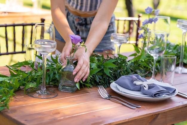 Przygotowanie do imprezy na świeżym powietrzu. dziewczyna ozdabia stoły świeżymi kwiatami. szczegóły dekoracji