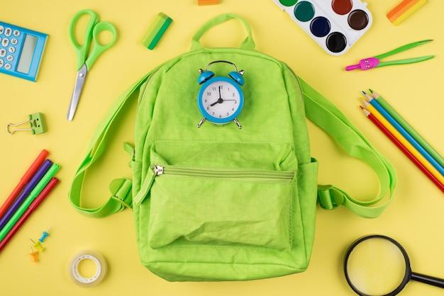 Przygotowanie do koncepcji szkoły. widok z góry na zdjęcie niebieskiego budzika, zielonego plecaka, kolorowej papeterii na żółtym tle