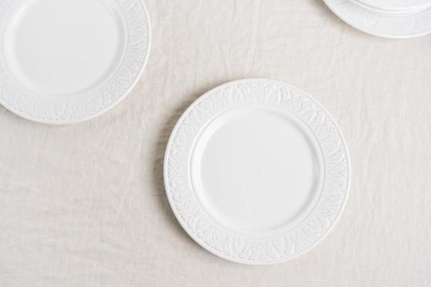 Przygotowanie do nakrycia stołu z białymi pustymi talerzami na lnianym obrusie z miejsca na kopię. koncepcja serwowania stołu z jedzeniem. widok z góry.