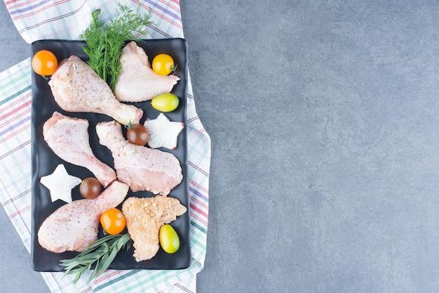 Przygotowanie do obiadu z talerzem surowych udek z kurczaka.